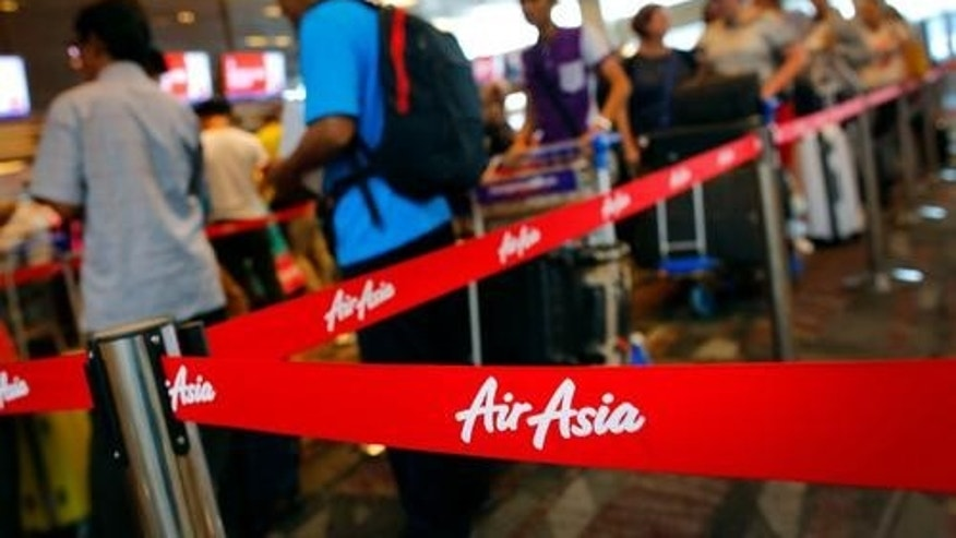 AirAsia passengers line up December 29 at Changi International Airport in Singapore, a day after the disappearance of Flight QZ8501.