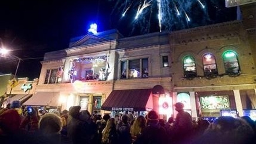 The crowd cheers and fireworks explode in the sky as a lighted cowboy boot drops to the roof of the Palace Saloon New Year's Eve on Whiskey Row in downtown Prescott, Ariz. on Dec 31, 2013.