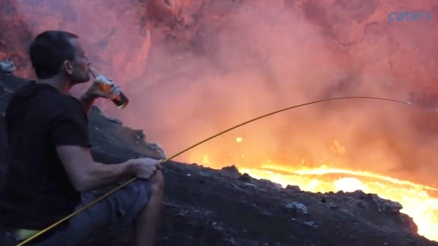 Simon Turner sits by an active lava lake to roast a marshmallow.