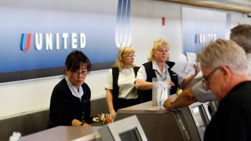 Customers check-in at a United ticket counter.