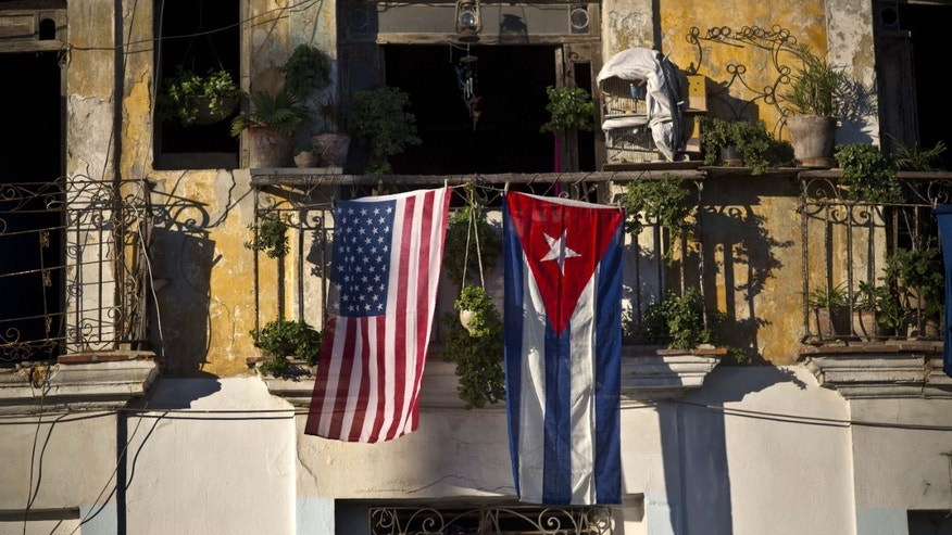 An American flag and a Cuban flag hang from a balcony in Old Havana.