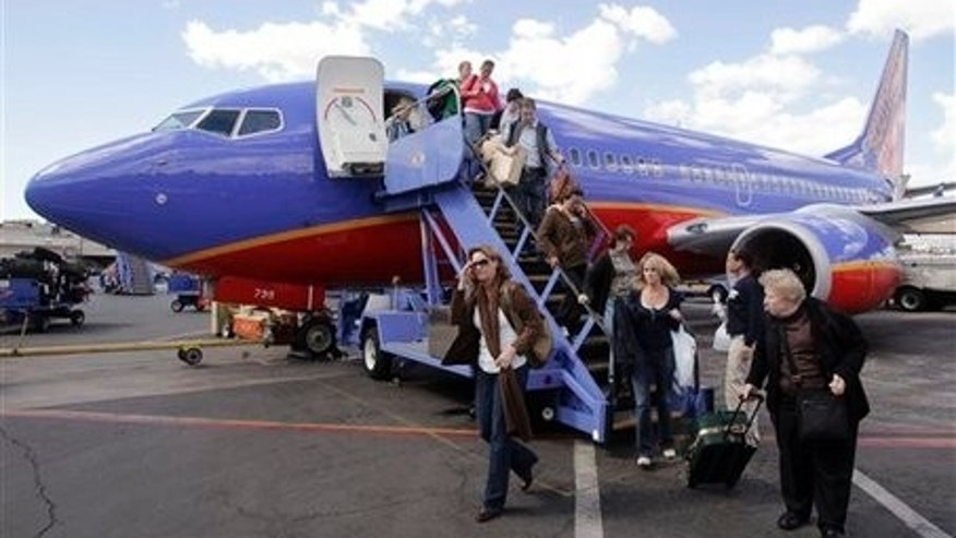 Passengers disembark a Southwest plane with carry-on luggage.