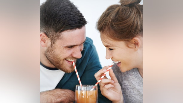 Shot of an attractive young couple sharing a milkshake together