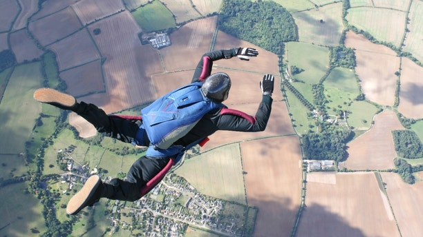 Skydiver in freefall high up in the air on a sunny day