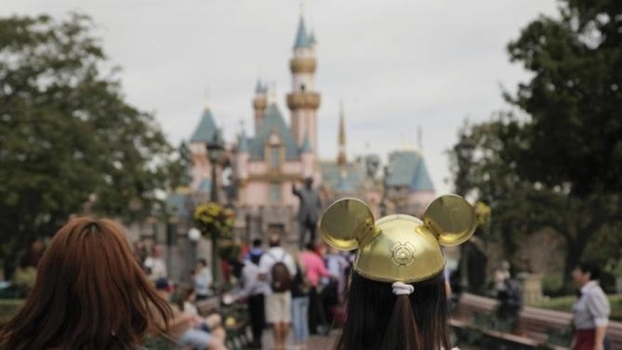 A woman at Disneyland walks towards Sleeping Beauty's Castle.
