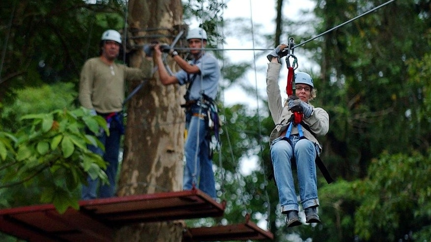 FILE - In this Jan. 28, 2005 file photo, Dutch tourist Carolyn Dorsman, right, rides through the canopy of the tropical forest, as her husband Wim Dorsman, left, and Costa Rican guide Esteban Cedeno, center, look on at the Arenal Volcano near La Fortuna, Costa Rica, north of the capital of San Jose. Zip lining through the Costa Rican rainforest is an extremely popular pursuit among tourists. (AP Photo/Kent Gilbert, File)