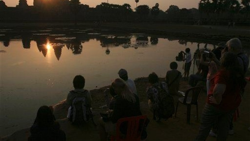 In this March 30, 2008 photo, tourists watch the sunrise at the famed Angkor Wat temple in Siem Reap province, Cambodia.