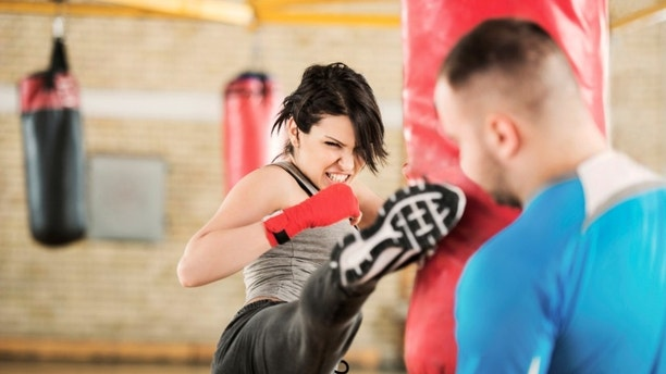 Young woman practicing boxing with her instructor. 