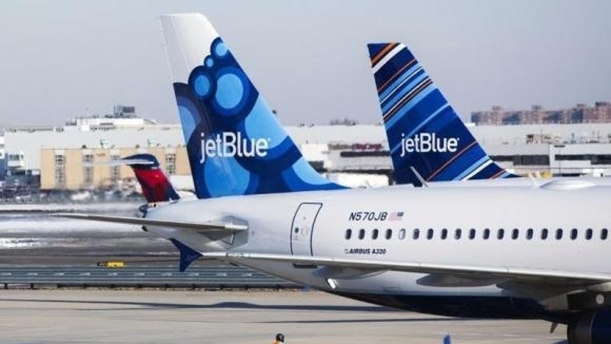 An airport worker leads JetBlue planes onto the tarmac of the John F. Kennedy International Airport in New York City.