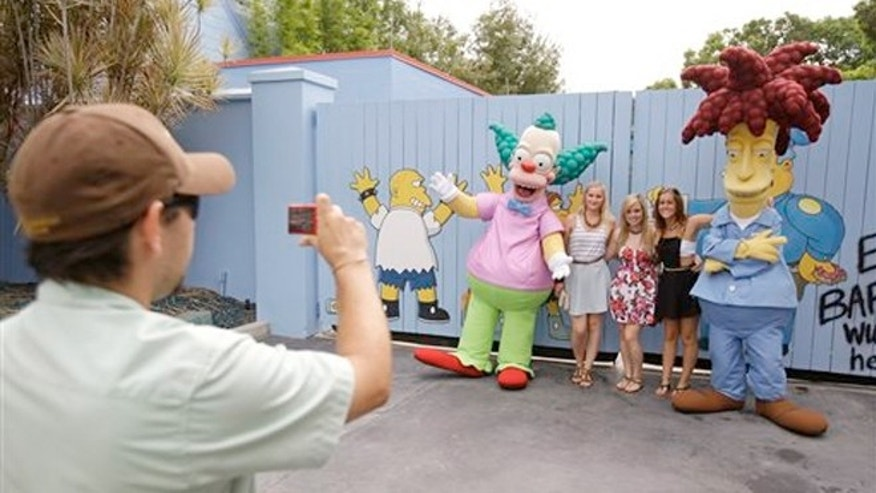 "FILE: A park employee taking a photo of guests with characters from the animated series ""The Simpson's"" at Springfield USA at Universal Studios Florida, Thursday, Sept. 5, 2013, in Orlando, Fla."