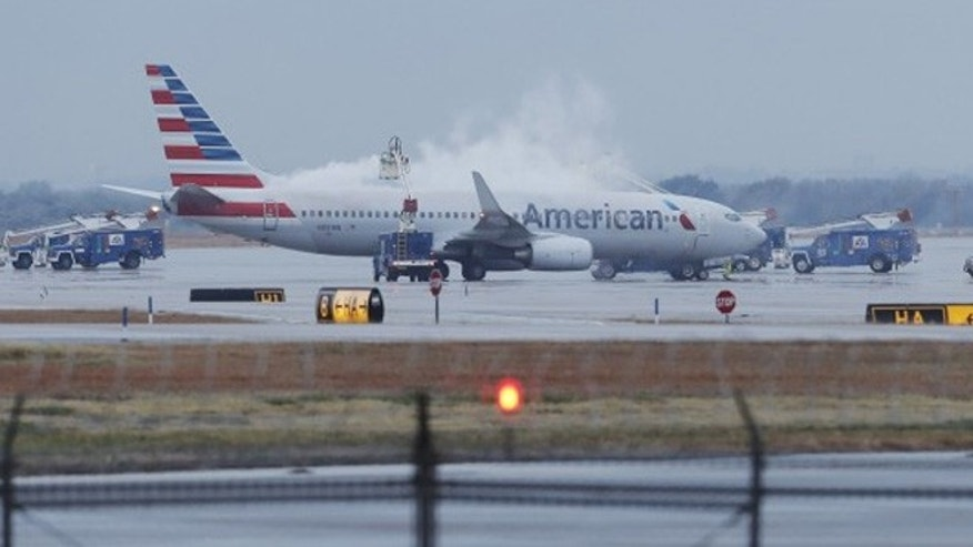 FILE: Crews spray deicing solution onto an American Airlines 737 before departure at Dallas-Fort Worth International airport.
