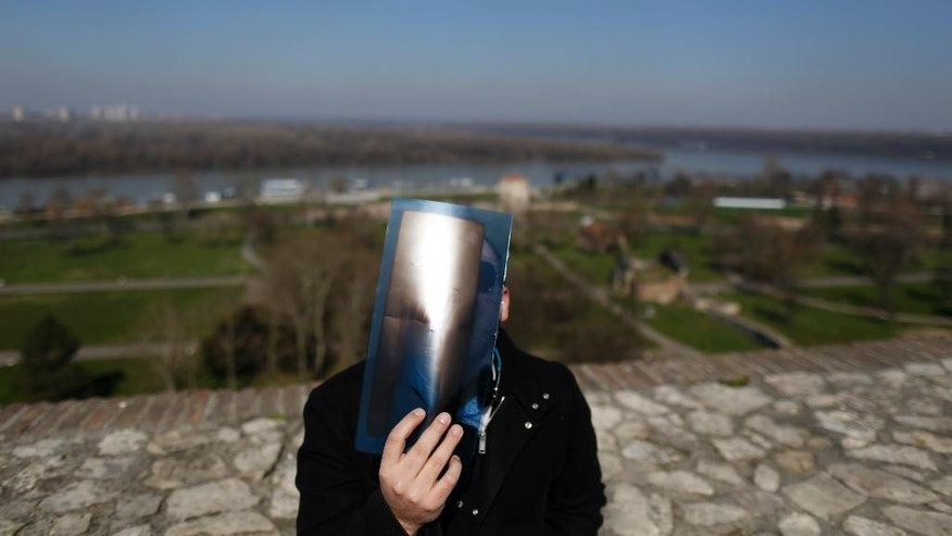 March 20, 2015: A man watches the partial solar eclipse trough an X ray film at the Kalemegdan citadel in Belgrade, Serbia.