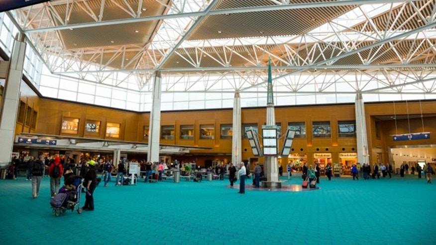 Travelers walk over the iconic green carpet of Portland International Airport in 2014.