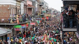 Mardi Gras crowds flood Bourbon Street.