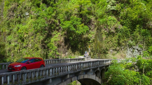 In this Sept. 24, 2014 photo, a car crosses a stone bridge on the Hana Highway in Hana, Hawaii. The road cuts through Maui's valleys and mountains and slithers above its coastal shores. The drive winds past long stretches of swaying sugar cane fields and blue ocean views with kite surfers soaring through the sky.  The notorious curves don't appear until well into the drive when the fields and ocean give away to tropical flowers and jungle greens. (AP Photo/Marco Garcia)