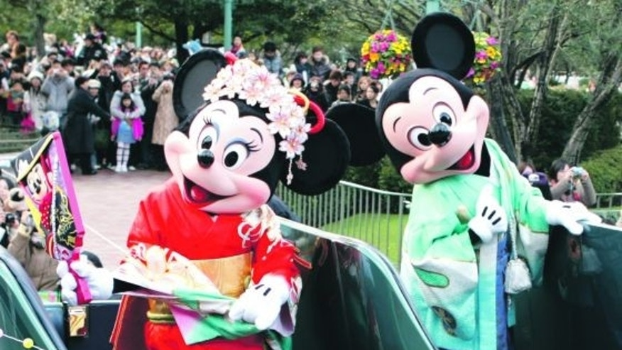 Mickey and Minnie Mouse don traditional kimonos for a parade through Tokyo Disneyland.
