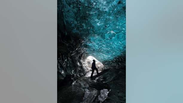 Skaftafell, Iceland - 10 December 2012: Man silhouetted standing inside  ice cave with textured blue and black ash ice walls gleaming, sand and clear ice floor leading to cave exit at Skaftafell, Iceland