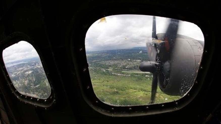"Two of the four engines of a Boeing B-17 ""Flying Fortress"" bomber are shown through a window May 5, 2014, as it flies near Seattle."