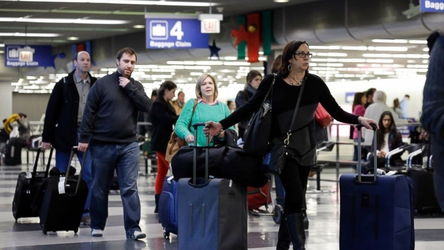In this Dec. 1, 2013 file photo, travelers walk through terminal 3 baggage claim at O'Hare International airport in Chicago.