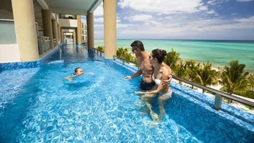 A family enjoying the upper-level oceanfront infinity swim-up suites, Riviera Maya, by Karisma.