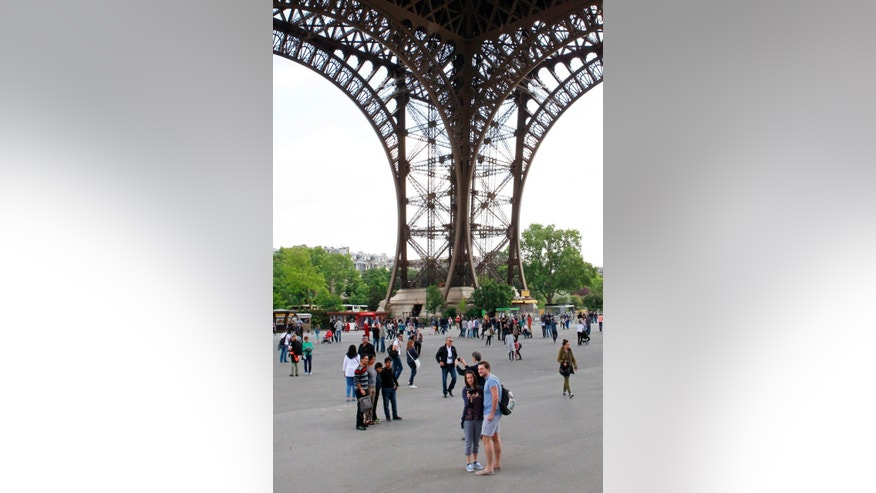 May 22, 2015 - Tourists wander under the Eiffel Tower, in Paris. The Tower is closed to the public because workers are protesting a recent rise in aggressive pickpockets.