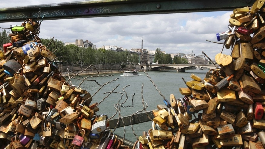 The Eiffel tower appears through the partly lock-free railing of the famed Pont des Arts bridge in Paris, Monday June 1, 2015.