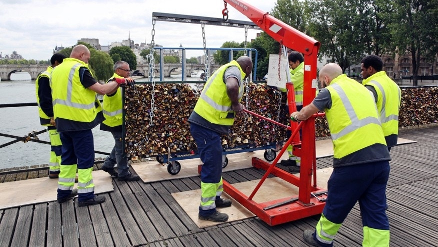Paris city employees remove a railing loaded with locks on the famed Pont des Arts bridge in Paris, Monday June 1, 2015.