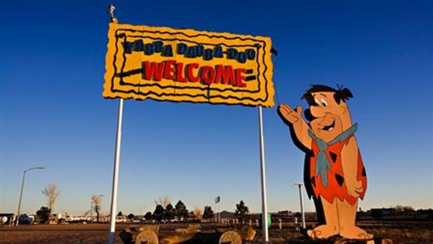 Fred Flintstone welcomes visitors to Bedrock City.