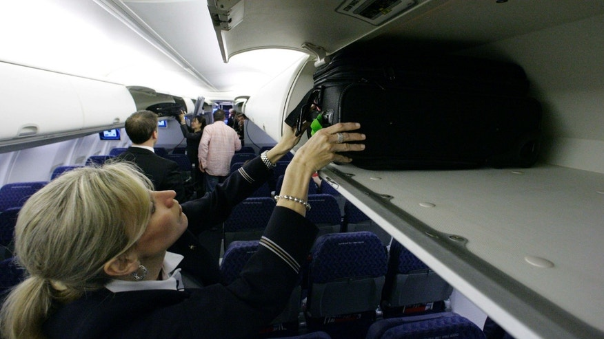 April 13, 2009:  American Airlines flight attendant Renee Schexnaildre demonstrates the overhead baggage area during a media preview of the airline's new Boeing 737-800 jets, at Dallas Fort Worth International Airport in Grapevine, Texas.