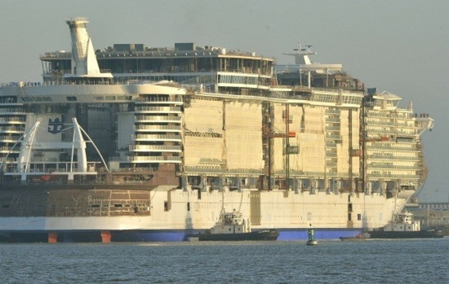 Harmony of the Seas being tugged out to sea after completion of exterior construction.