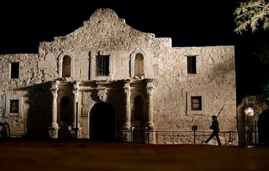 A member of the San Antonio Living History Association patrols the Alamo in a predawn ceremony, part of an observance of the anniversary of the 1836 battle there.