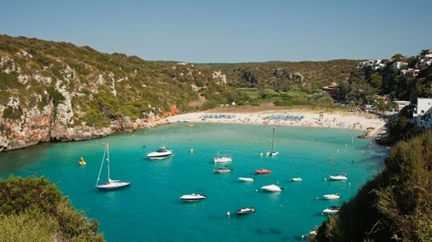Beach on a bay with aqua water, several boats. Suitable for the summer holiday concept