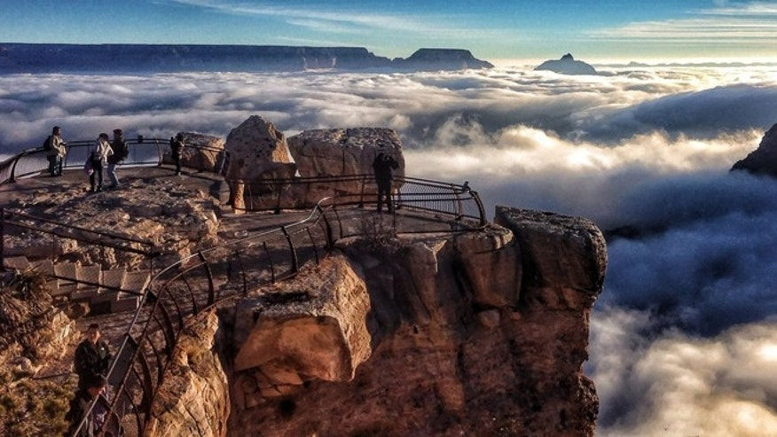Visitors to Mather Point at Grand Canyon National Park, Ariz. look out over a rare total cloud inversion in 2013.