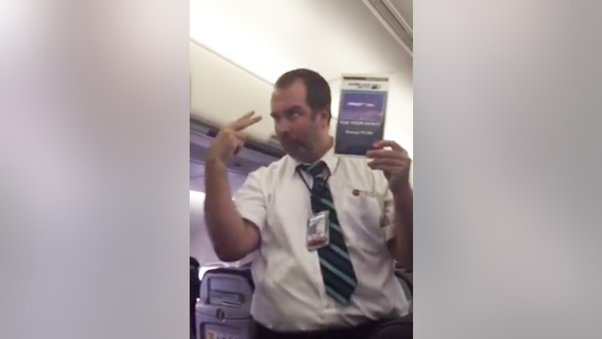 A flight attendant mid dramatic safety demonstration performance.