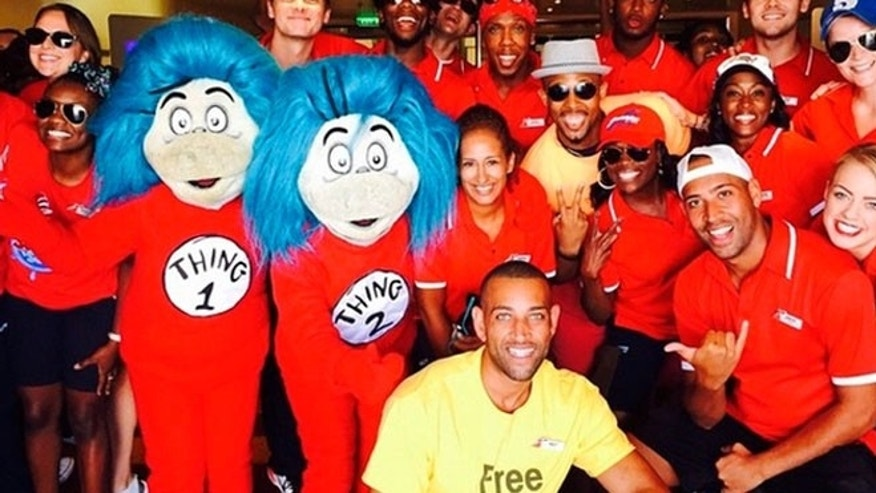 "Carnival Breeze cruise director Matt Mitcham (in the yellow ""Free Hugs"" shirt) with his entertainment staff and a couple of special guests."