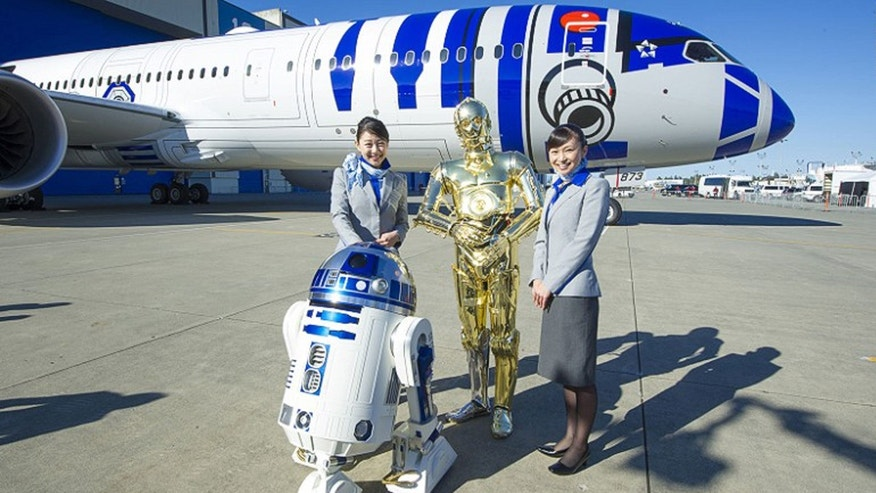 "Flight attendants pose in front of the aircraft with R2-D2 and C-3PO from ""Star Wars."""