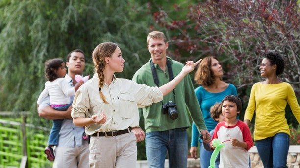 Multi-ethnic tourists with young children (3 to 7 years) visiting a park, walking with tour guide.  Focus on guide.