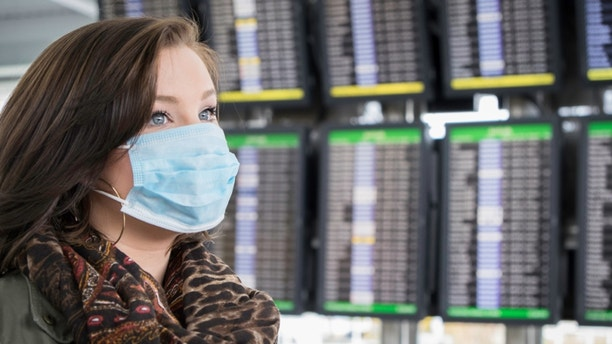 An attractive female wears a mask at the airport, possibly fearful of Ebola.
