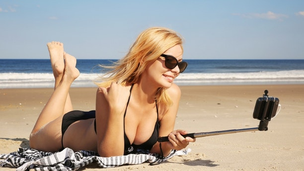 Young woman in bikini taking selfie photo with stick on the beach