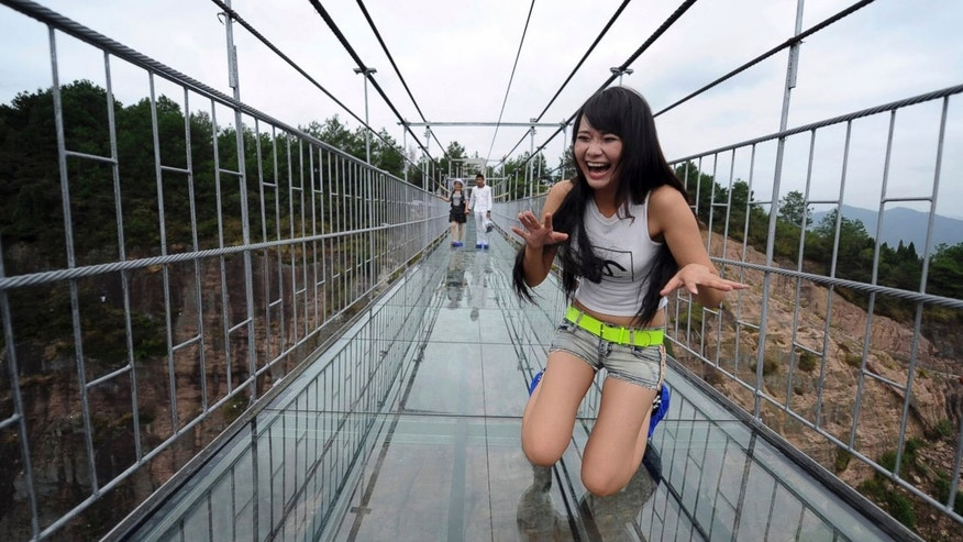 A visitor tries not to look down while crossing the glass walkway.