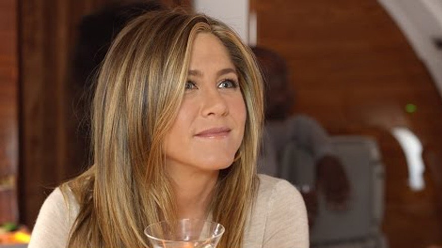 Jennifer Aniston enjoys a cocktail aboard an Emirates airplane at the bar.