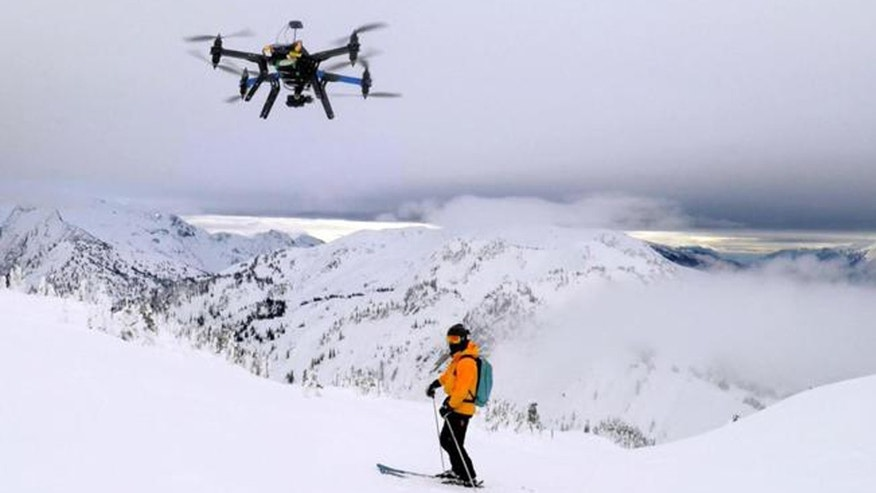 A drone camera hovering by a skier as he makes his way down mountainside at resort at Revelstoke, B.C., Canada in Dec. 2014.