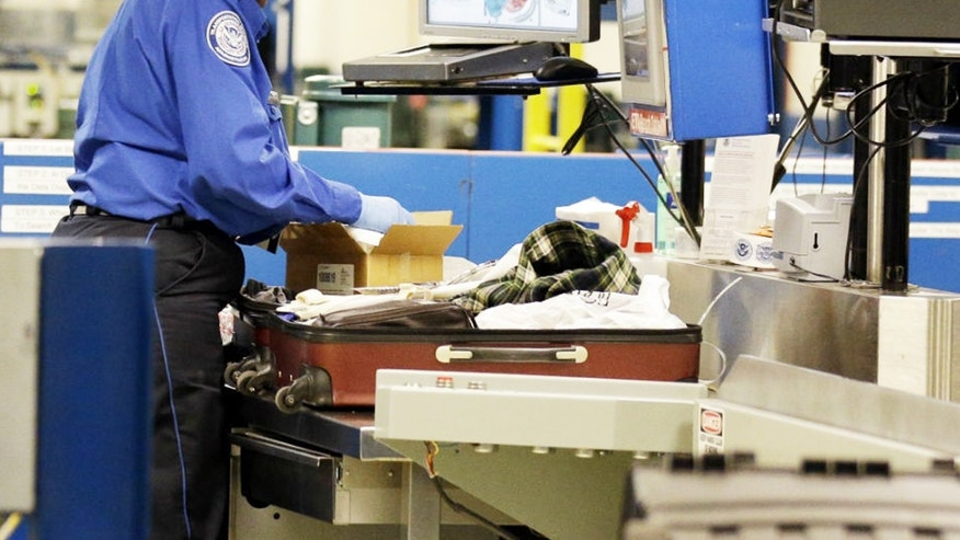 A TSA agent inspects a package inside a suitcase.