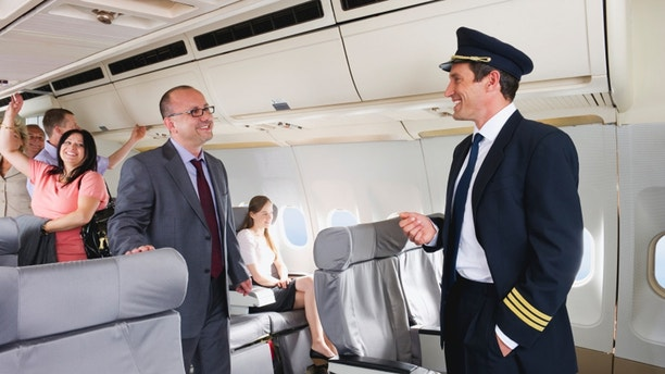 Flight captain talking with businessman on airplane