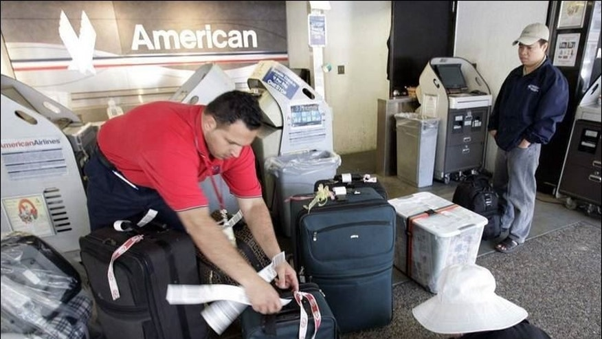 An American Airlines luggage handler helps passengers check in seven pieces at San Jose International Airport.