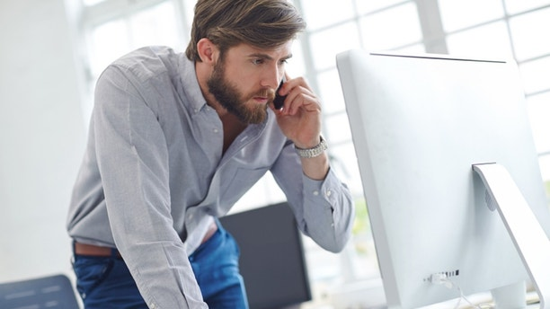 Shot of a designer talking on his phone while reading something on his computer screen