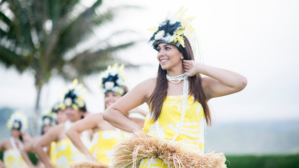Hawaiian cultural dancers doing a performance for tourists.