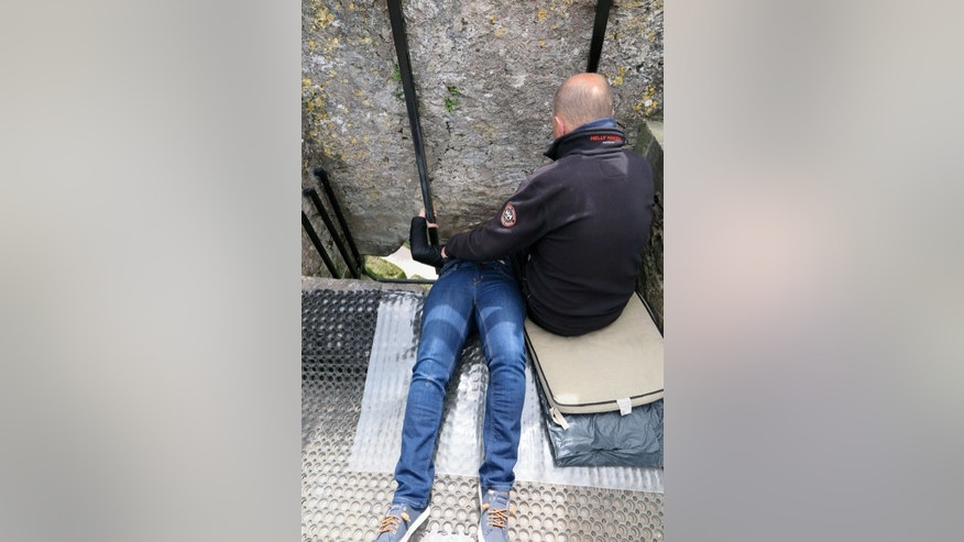 A woman bends backward to kiss the famed Blarney Stone.