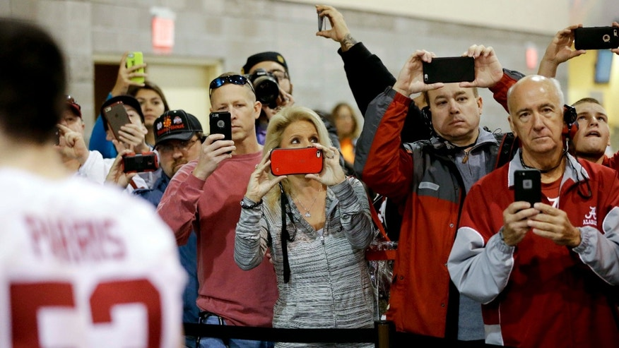Jan. 9, 2016: Fans take pictures as the team from Alabama leaves after media day for the NCAA College Football Playoff National Championship in Phoenix.