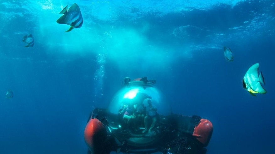 This December 2015 image supplied by Crystal Cruises shows a submersible sightseeing capsule in waters off the Seychelles islands, an excursion offered to passengers aboard the Crystal Cruises yacht Crystal Esprit. The glass pod carries two people plus a captain and the 30-minute ride is $599 a person. (Ian Schemper, Crystal Cruises via AP)